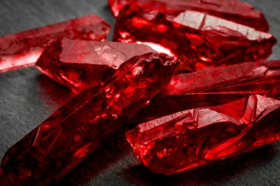 Rubies and raw crystal gems concept with closeup of a bunch of red rough uncut ruby crystals